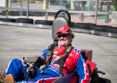 A man wearing a red hat riding on a kart