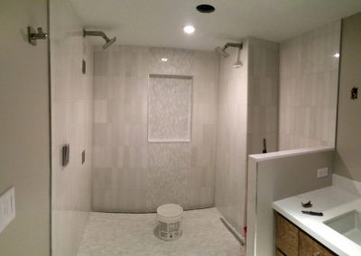 tile floor installation- shower that has a sink and a mirror