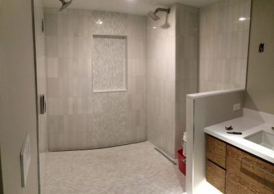 tile floor installation-shower that has a sink and a mirror