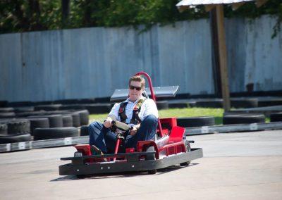 A man with a stripe shirt riding on a cart